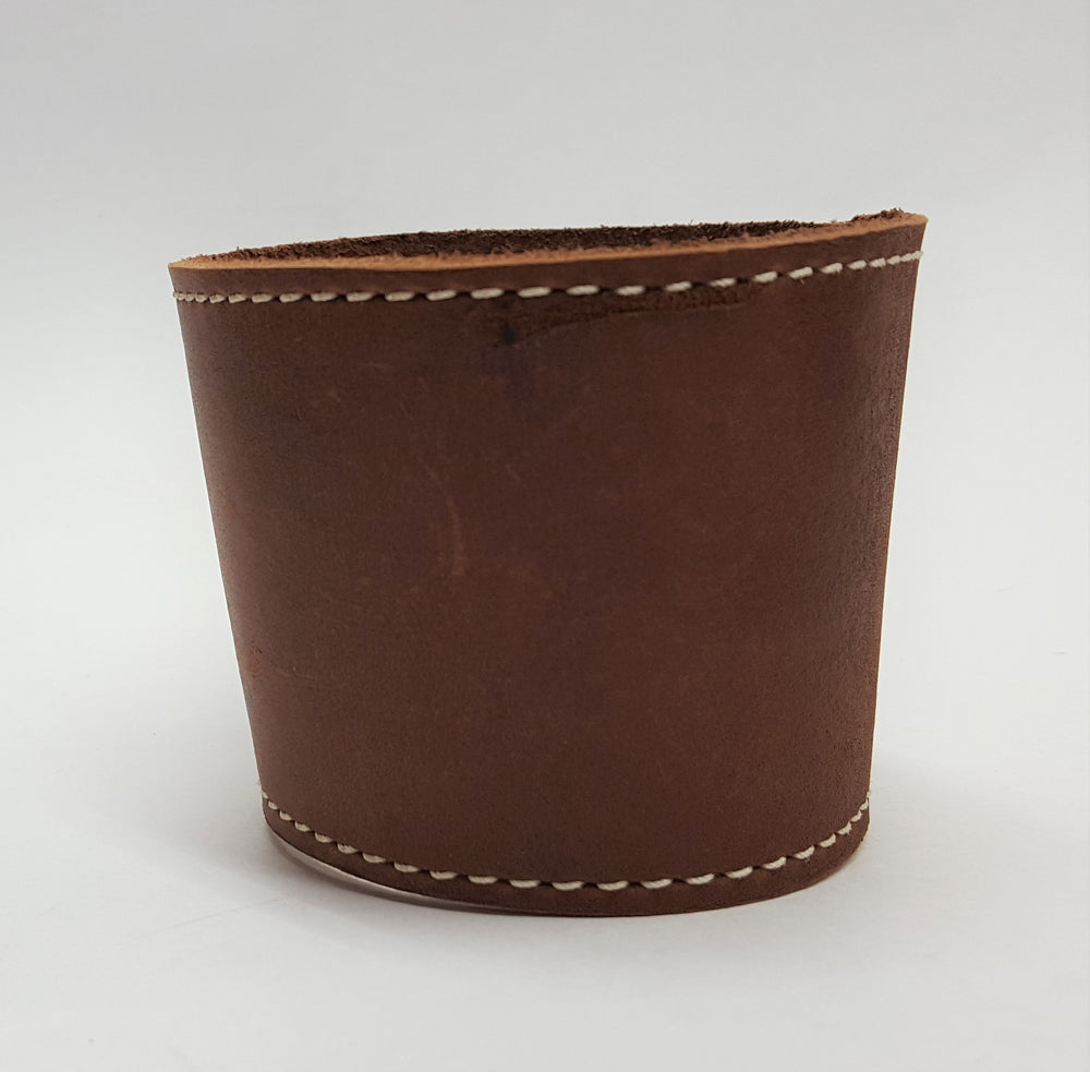 Brown leather coffee cup sleeve with silver colored rivets along connecting edge. Edges stitched with white contrasting thread. Alternate view. Made from brown cowhide in the shop just outside Nashville in Smyrna, TN