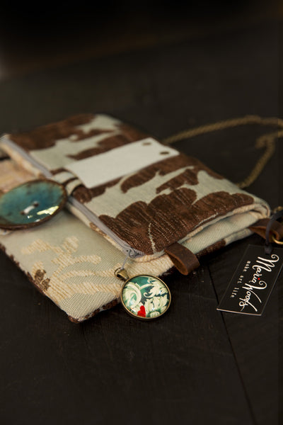 One-of-a-kind fold-over clutch/bag. Handmade wearable art in chocolate brown, ice blue and cream fabrics and leather accents.