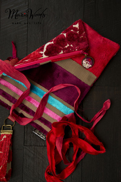 One-of-a-kind fold-over clutch. Handmade wearable art in shades of red and burgundy luxurious designer fabric.