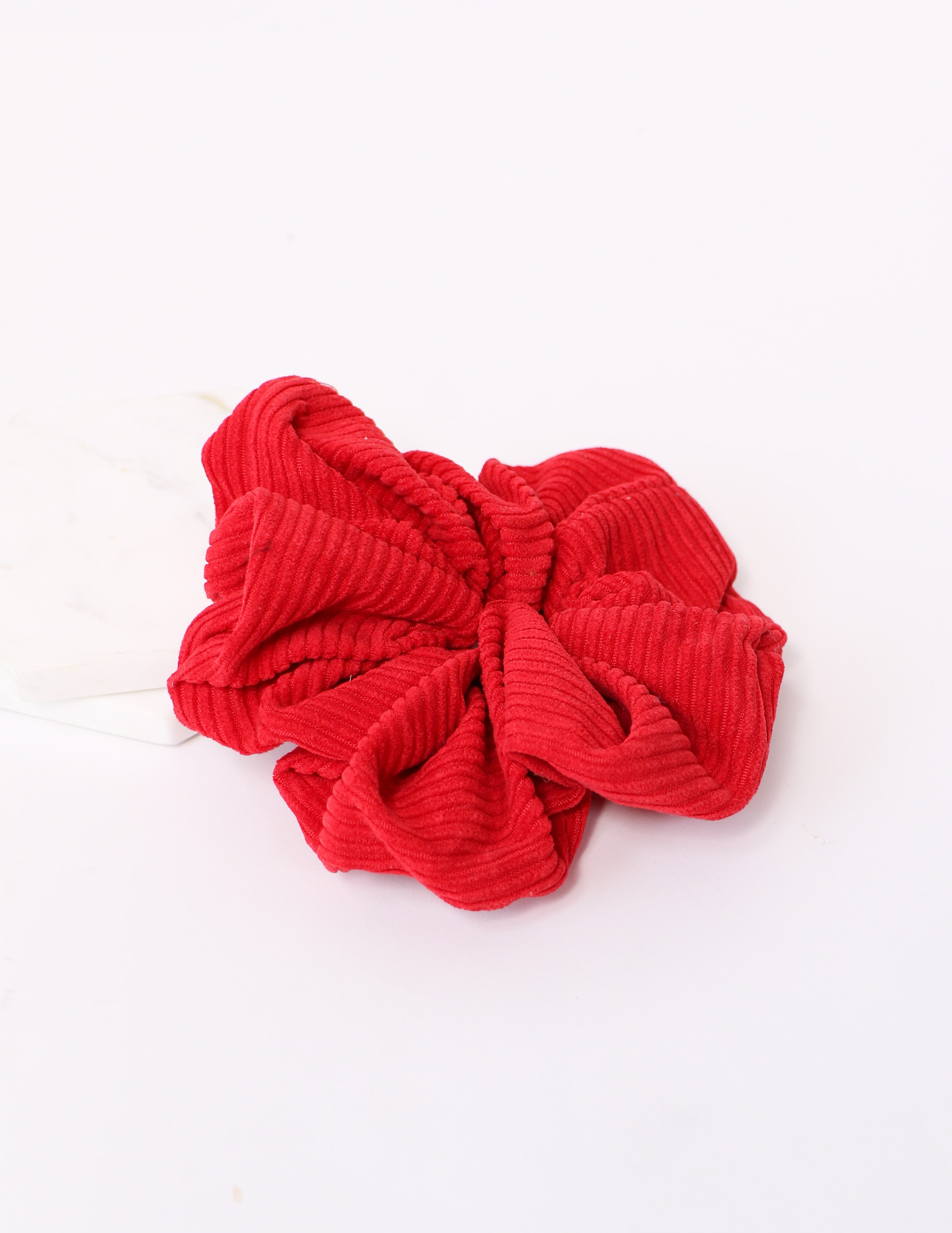 Red corduroy here nor hair scrunchie on white background - elle bleu
