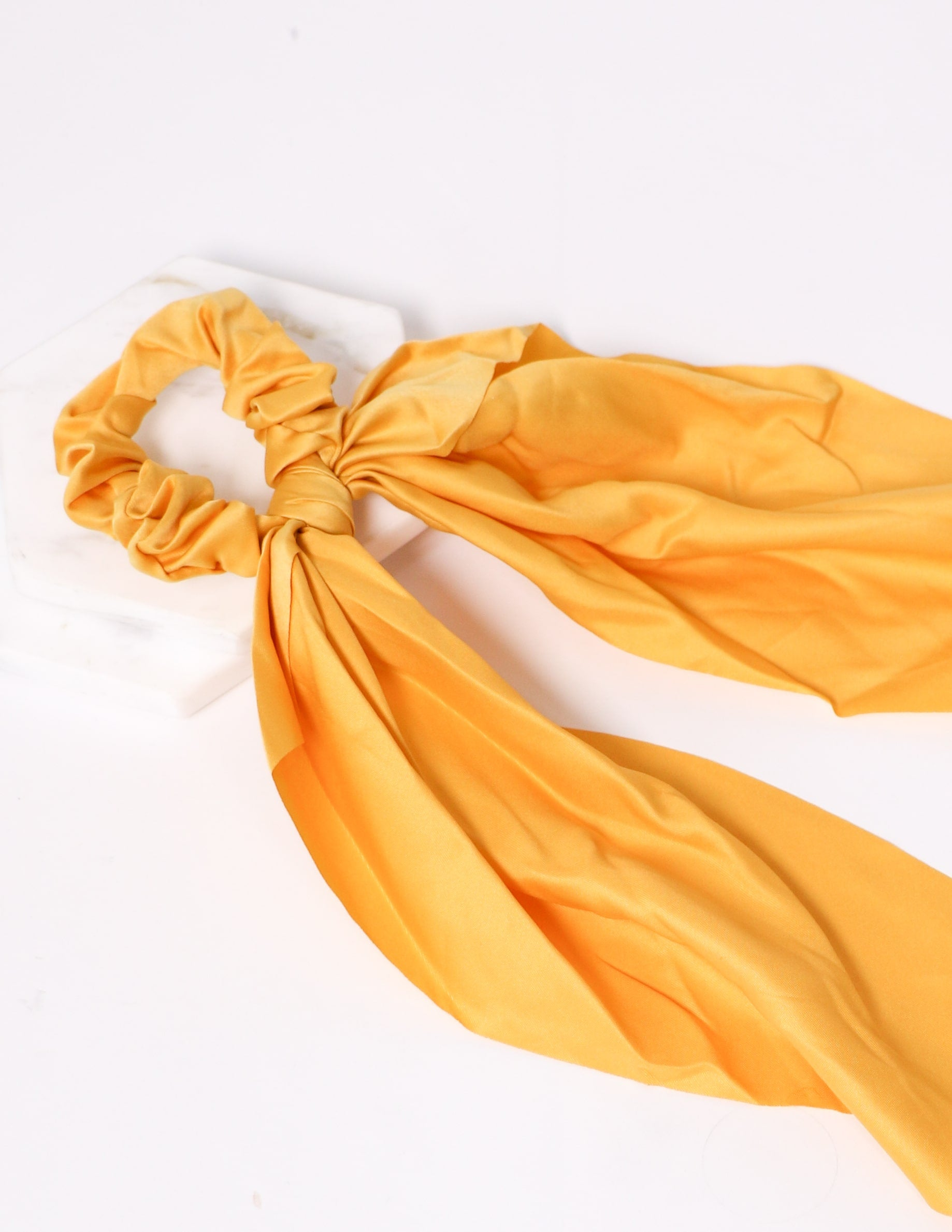 Close up of the mustard tie it up ribbon scrunchie on white background