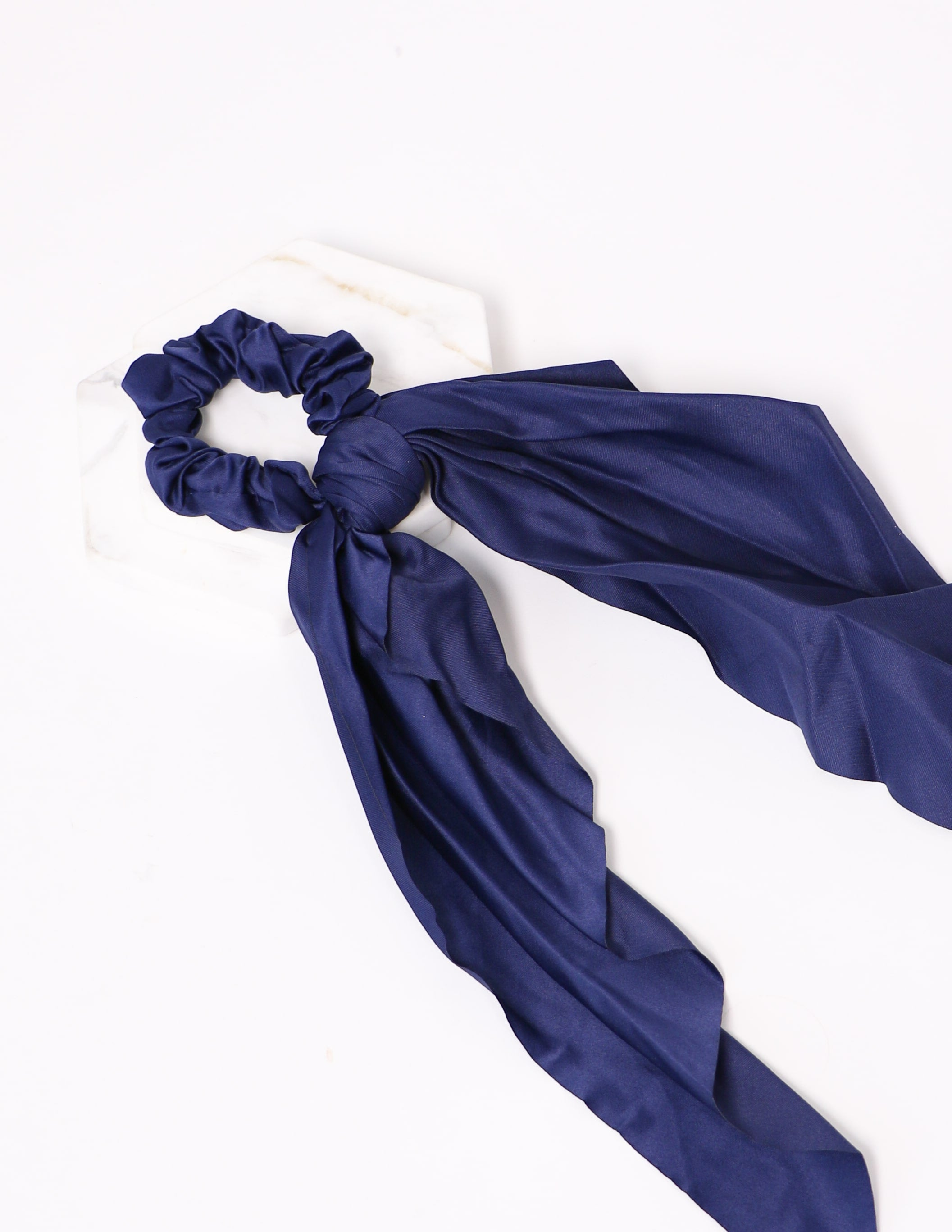 Close up of the tie it up navy ribbon scrunchie on white background