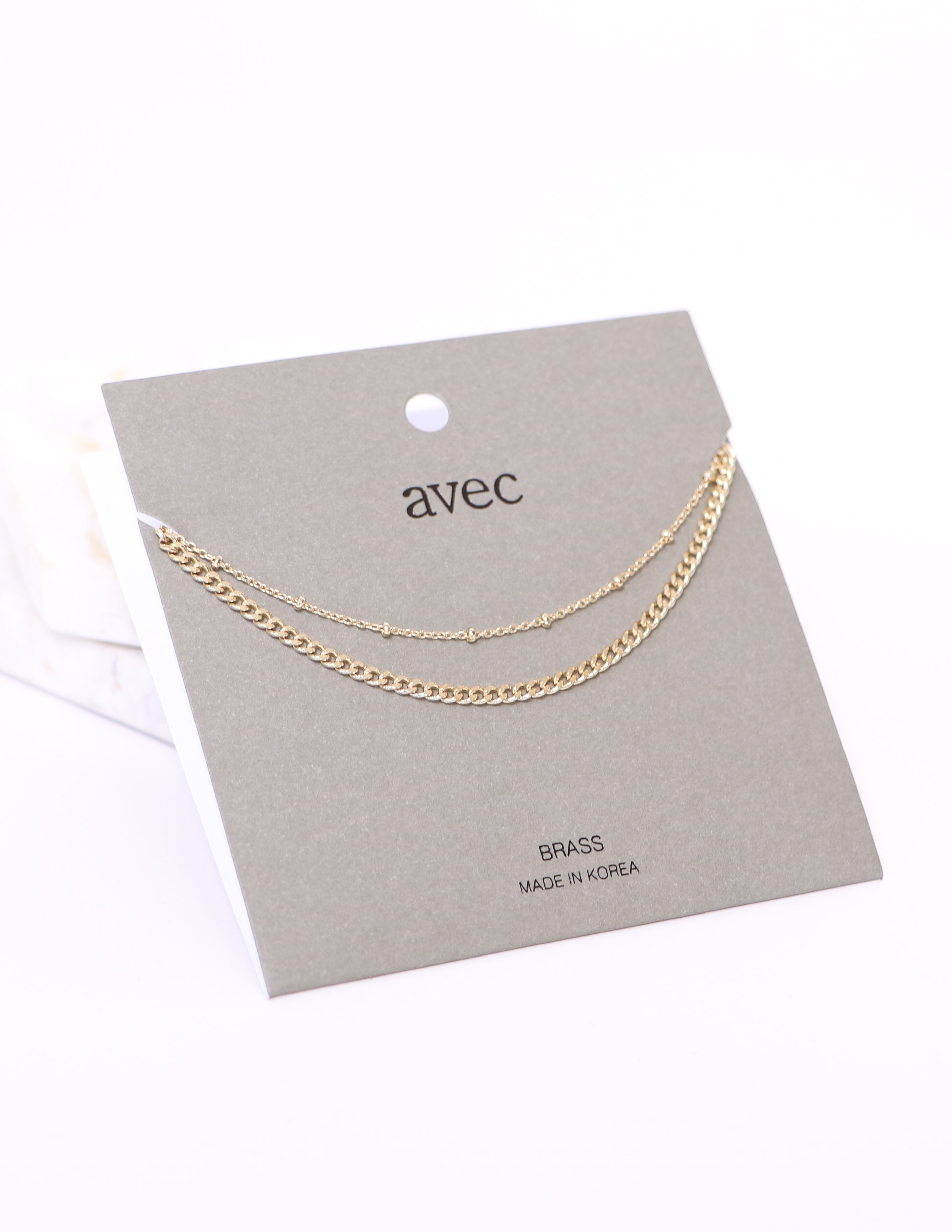 Layer eyes on this gold necklace on grey card packaging - elle bleu shoes