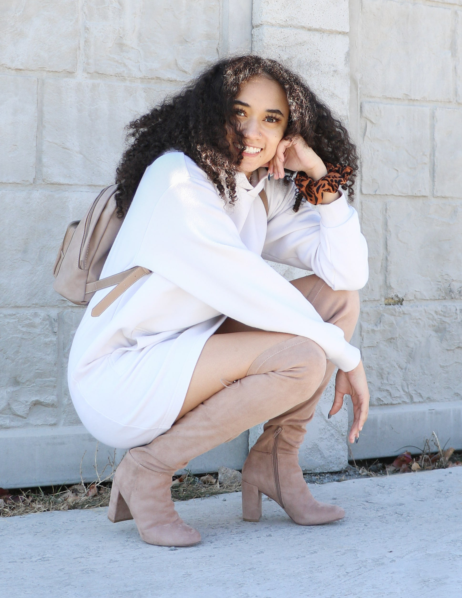 Model crouching in white hoodie dress and she's tall that taupe boots