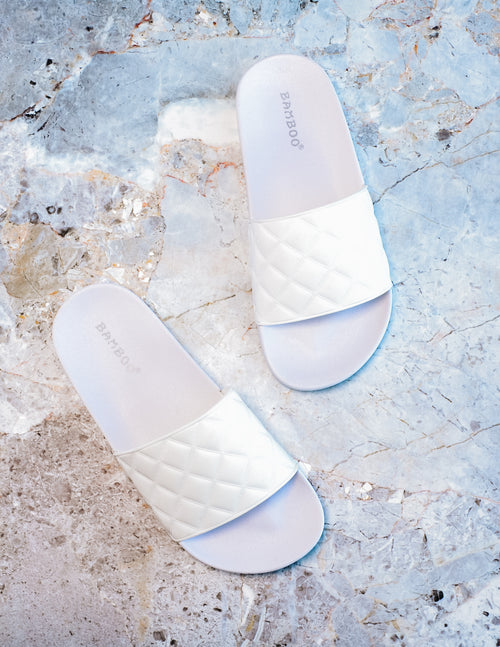 White quilted quilt poolin' around slides on marble stone background - elle bleu shoes