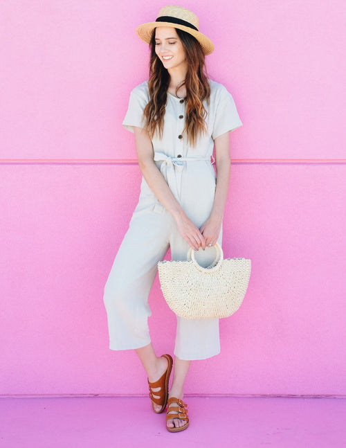 Model standing outside next to pink wall in jumper and tan slide sandals
