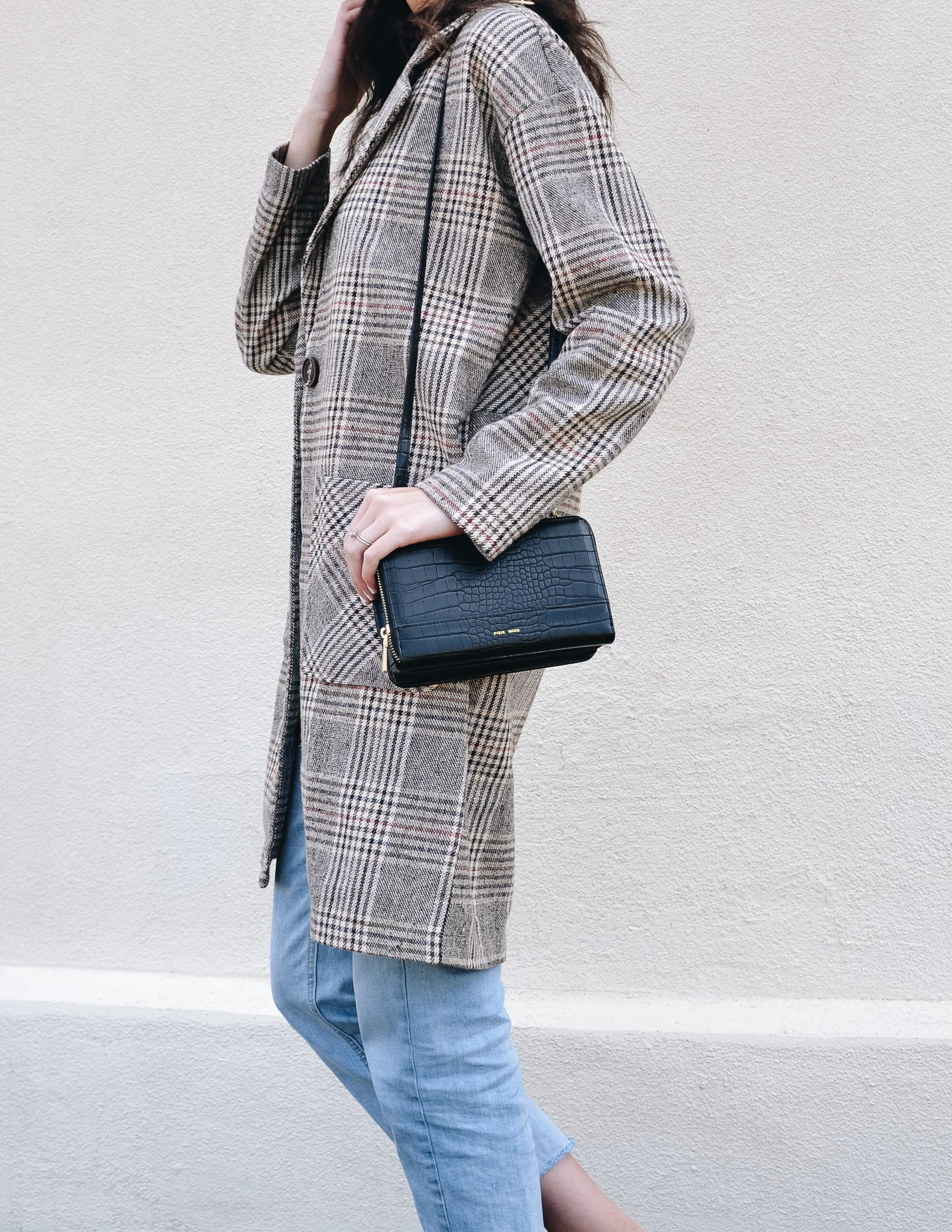 Model showing off the black crocodile jane purse in plaid coat and denim