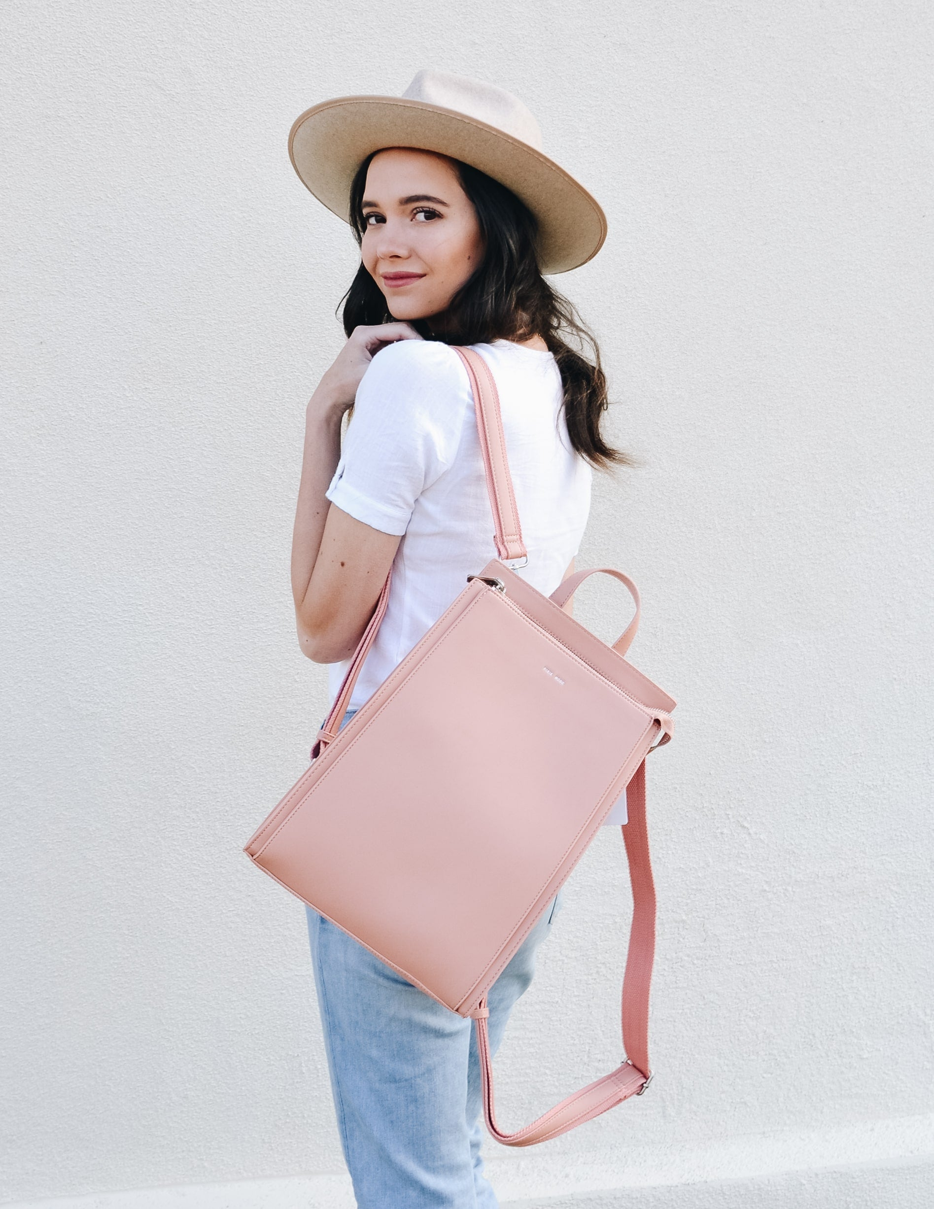 Model showing off apricot pixie mood carrie convertible backpack with one shoulder