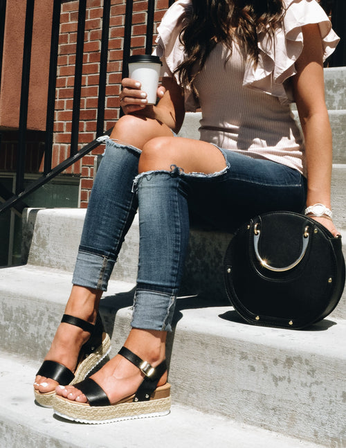 Model sitting on concrete steps wearing denim, blush top, and black platforms