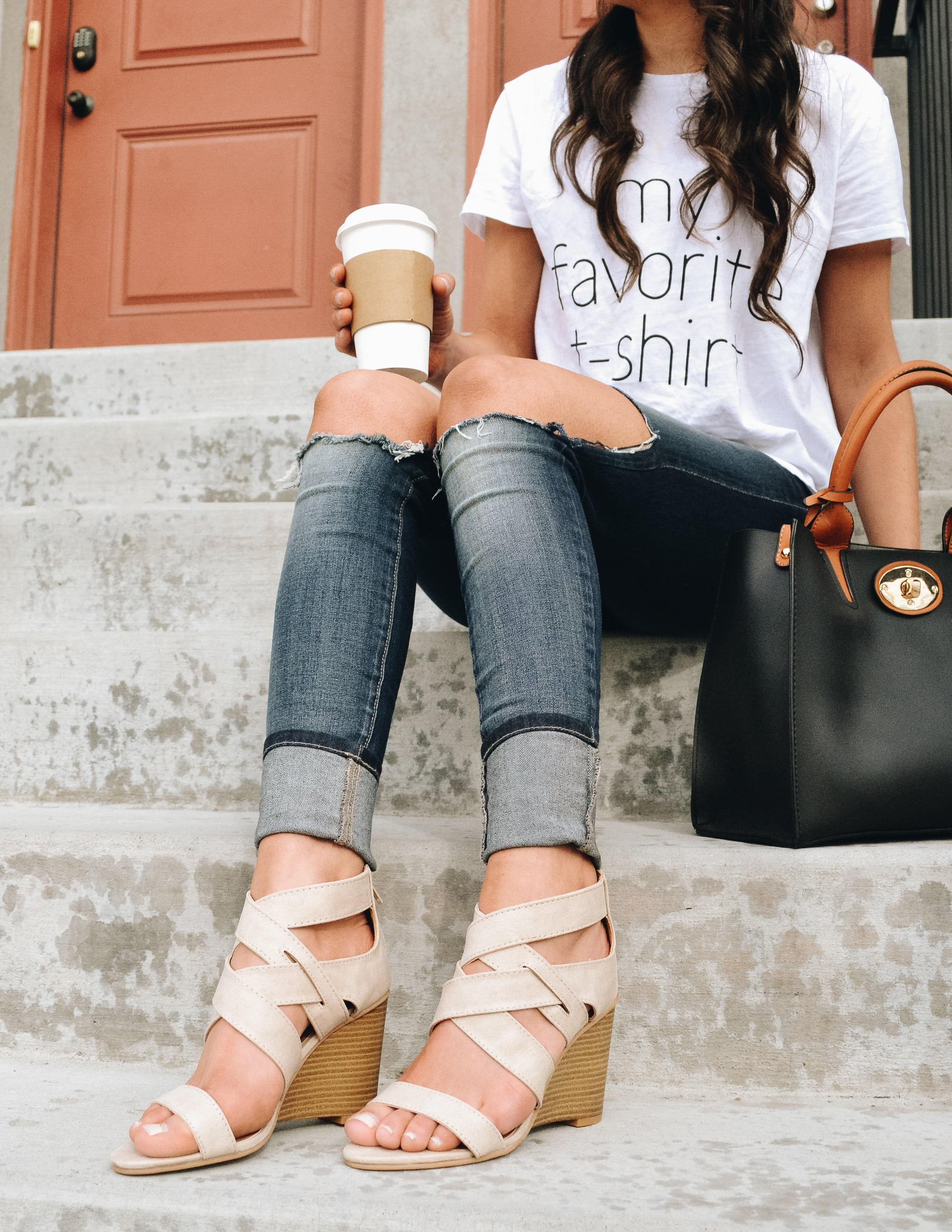 Model sitting on steps wearing tee, denim, and beige wedges
