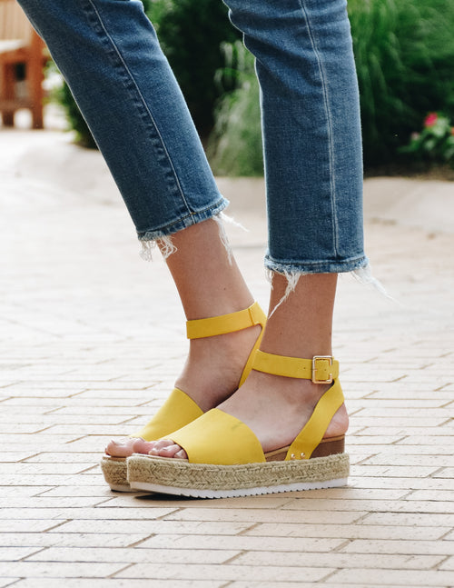 close up of the model standing in yellow aphrodite platform sandals - elle bleu