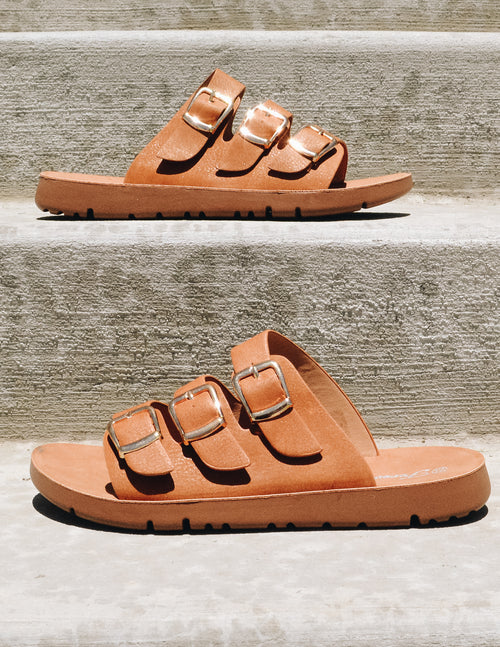 tan buckle slide sandal on concrete steps outside - elle bleu shoes