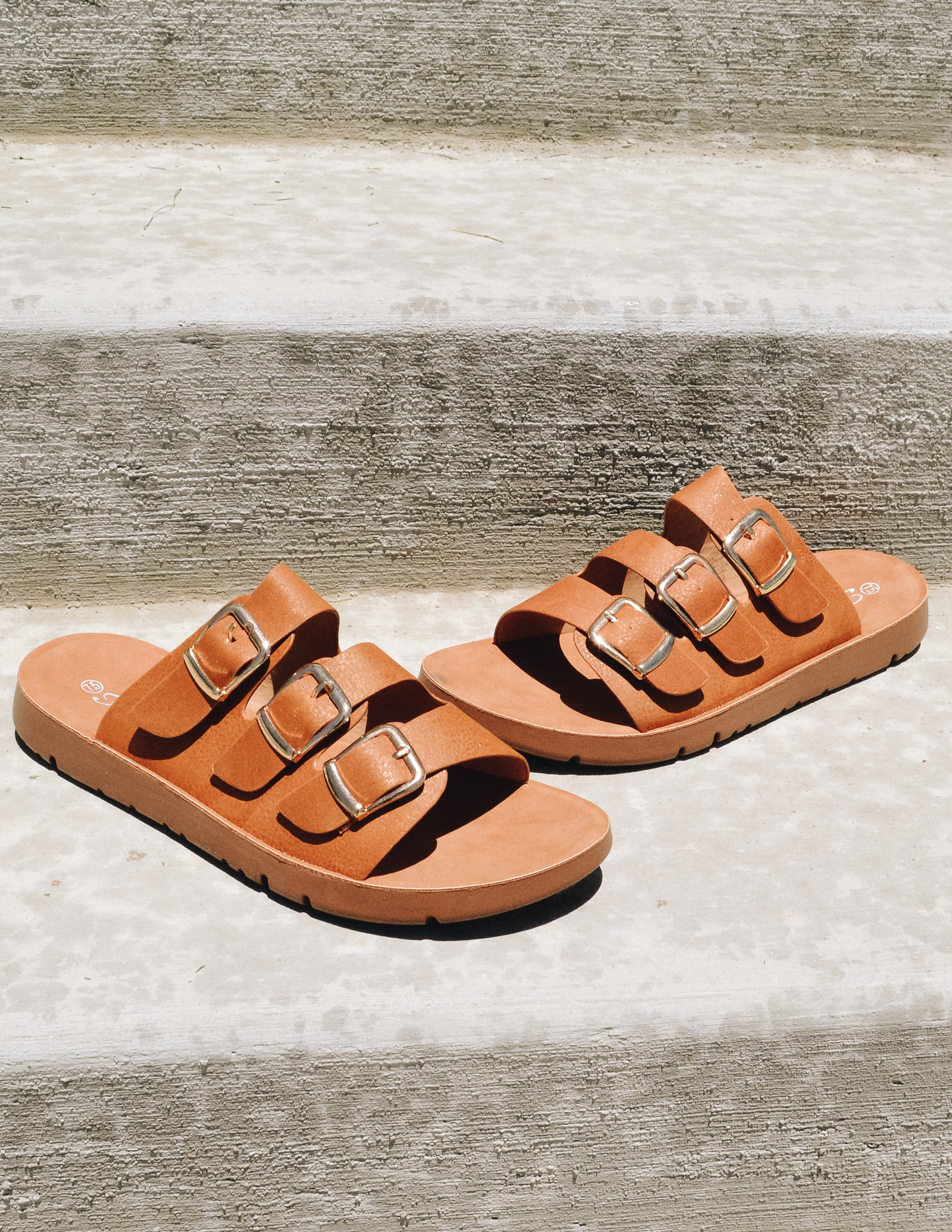 Tan sandals with three buckle straps outside on concrete steps - elle bleu shoes
