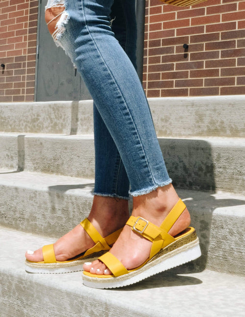 Girl standing outside on steps in yellow wedges and denim - elle bleu