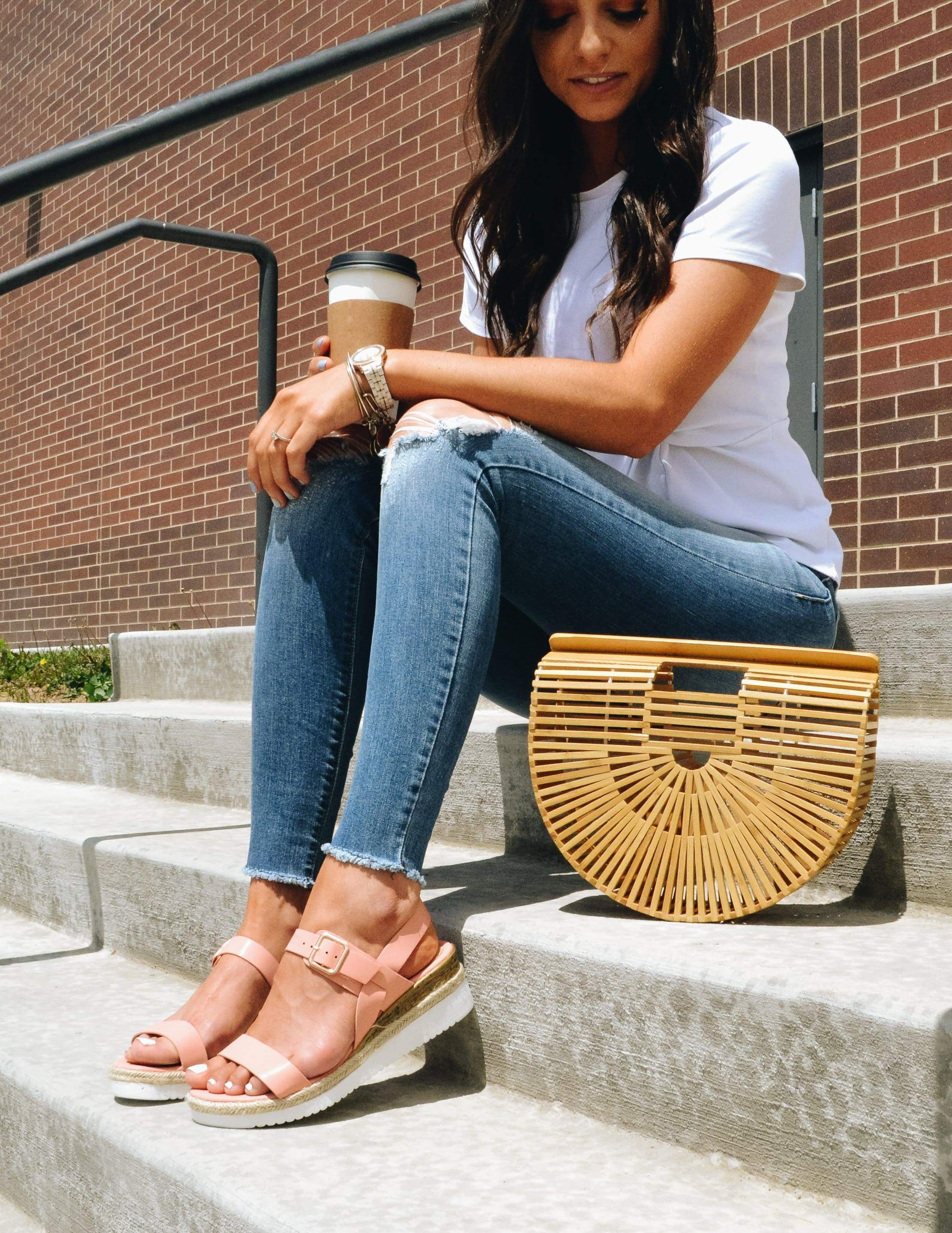 Model sitting outside holding coffee and tan purse - elle bleu shoes