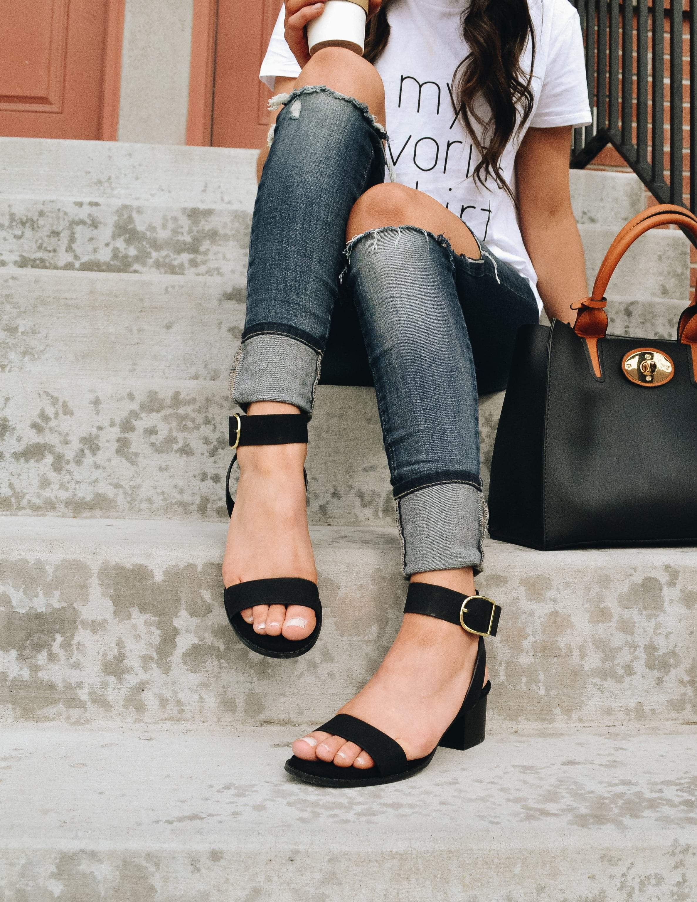 Model sitting on steps holding coffee and bag wearing denim and black heels
