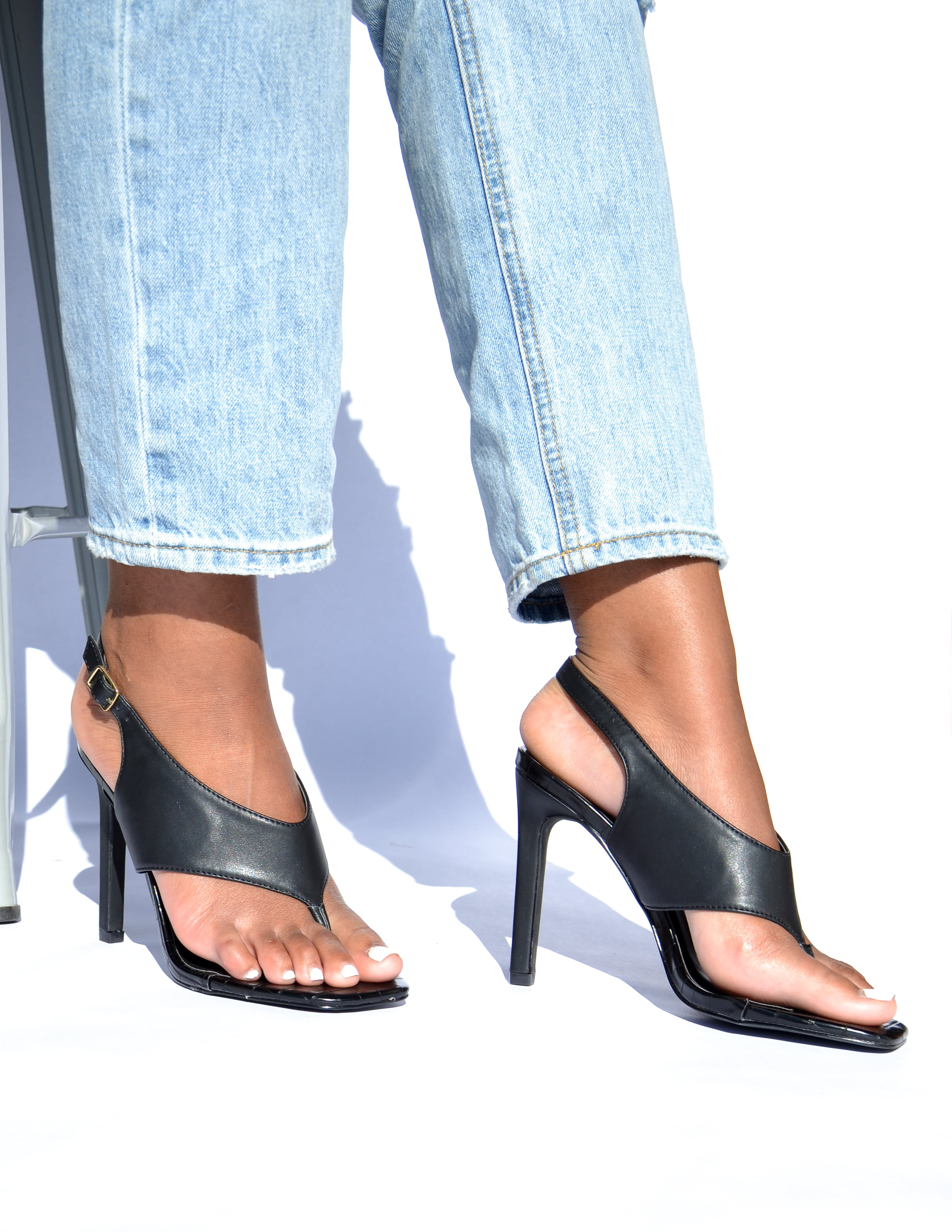 Model standing in black club can't sandal me heel  - elle bleu