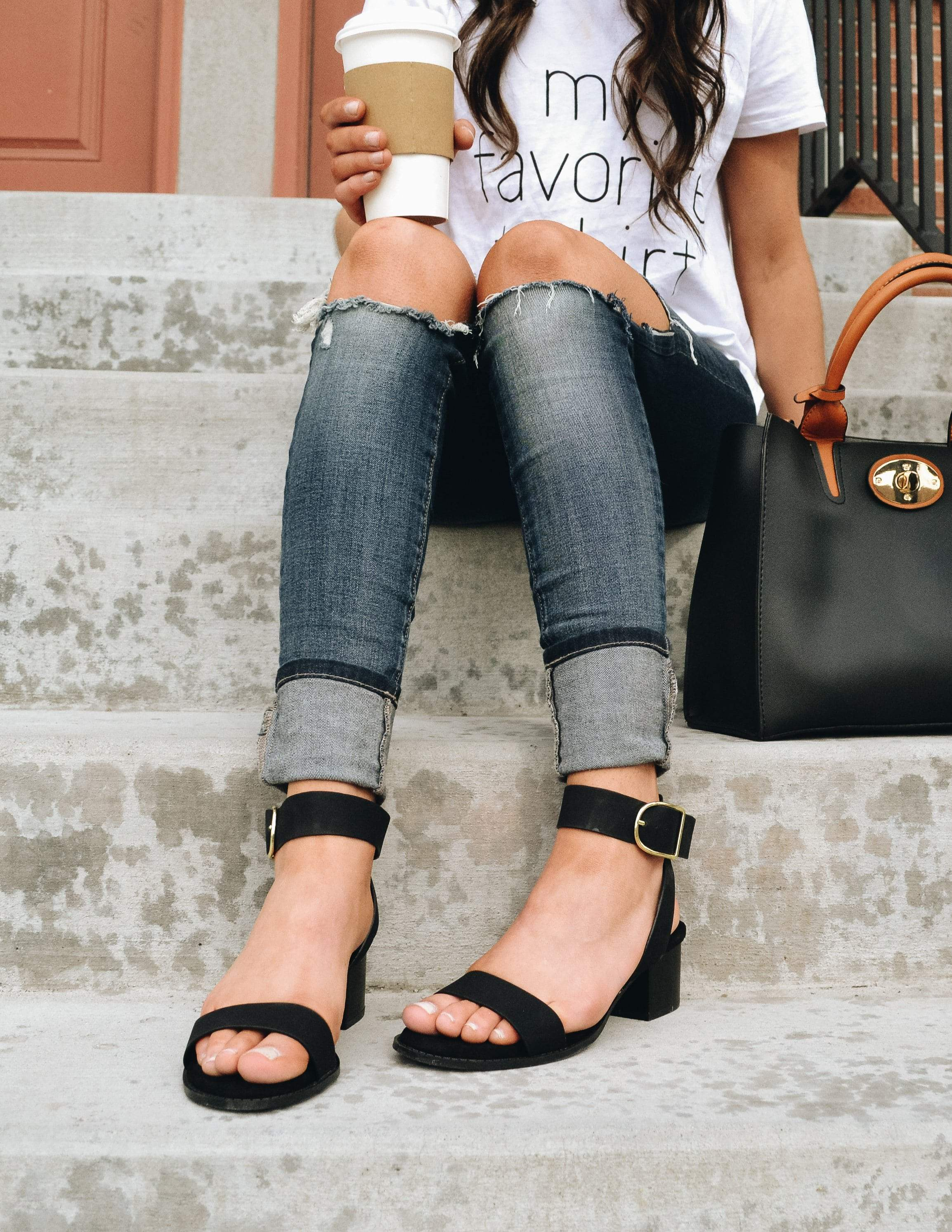 Model sitting on steps in tee, denim, and black strappy heels - elle bleu shoes