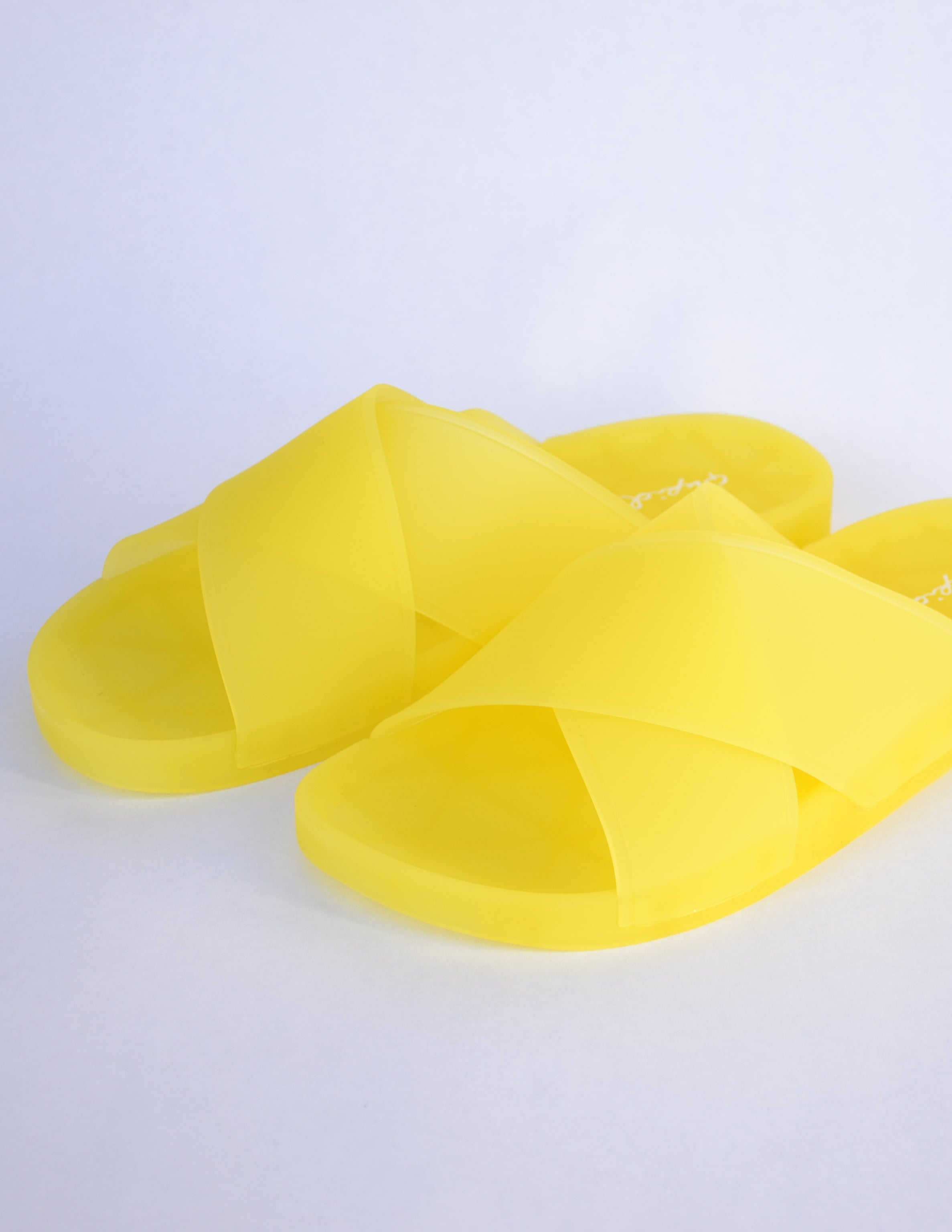 Yellow slide sandals with thick crossing straps over the top of the shoe