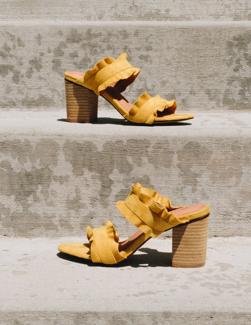 Mustard Mi.iM Rachel heels with two ruffle straps and stacked wood heel on concrete steps