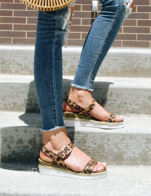 Girl standing on steps outside in denim and cheetah platform wedges