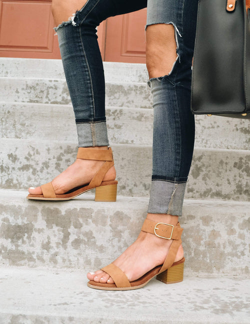 Knee down shot of model standing on steps in denim and camel rich girl heel