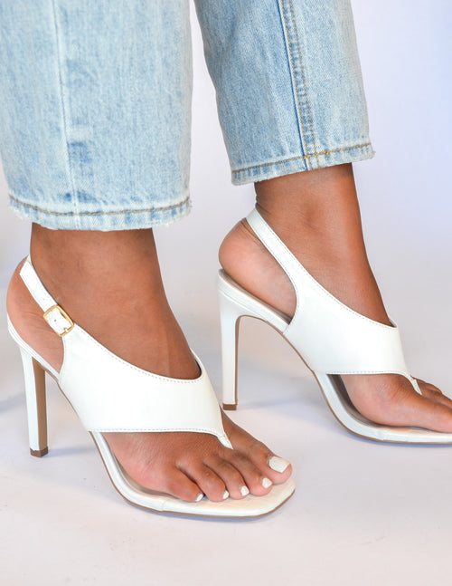 Closeup of model standing in white club can't sandal me heel