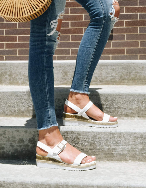 Girl standing with one foot on each step in denim and white wedges