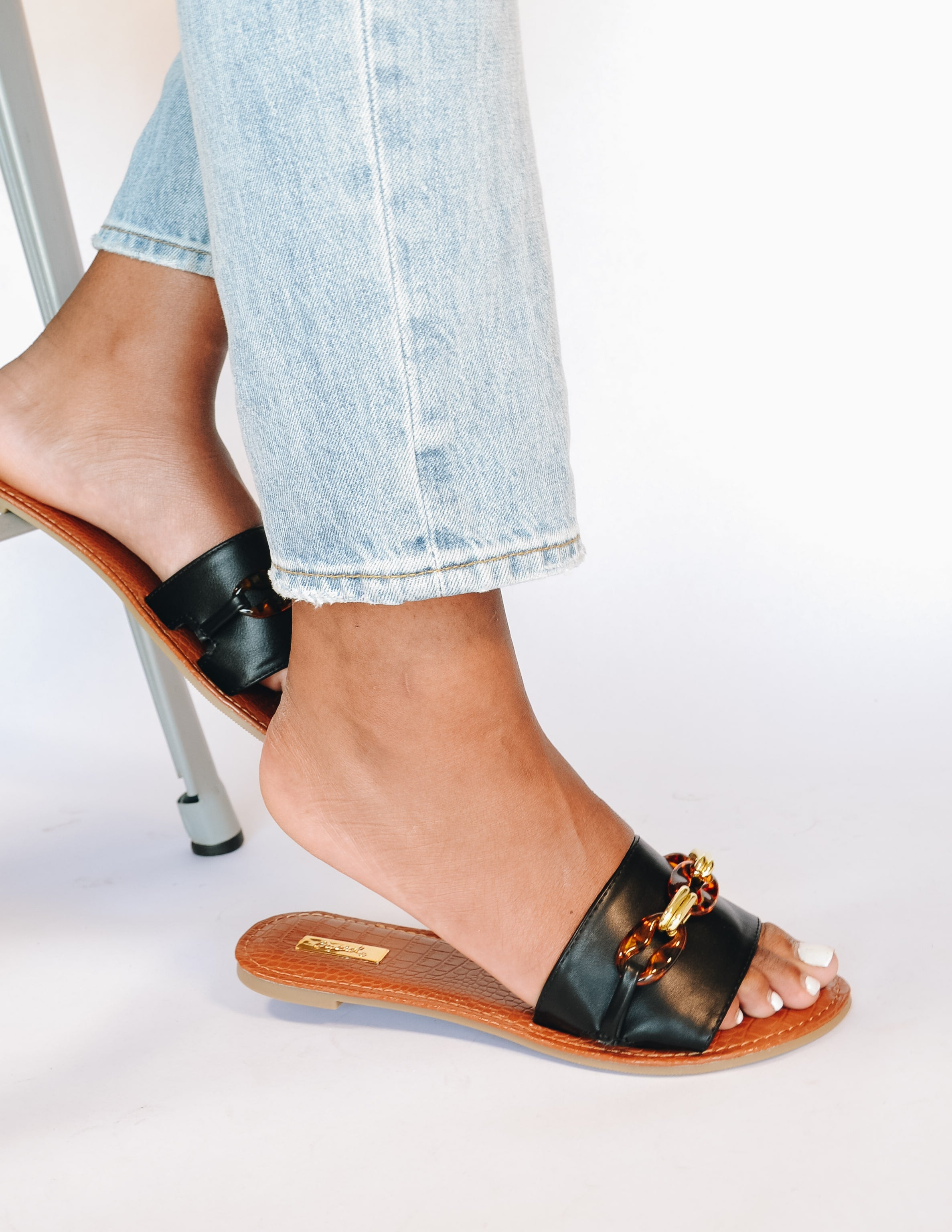 Model sitting in black tortoise shell buckle slide sandals and denim