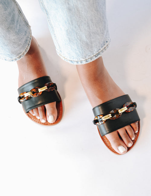 Top view of the black tortoiseshell and gold chain slide sandals - elle bleu shoes