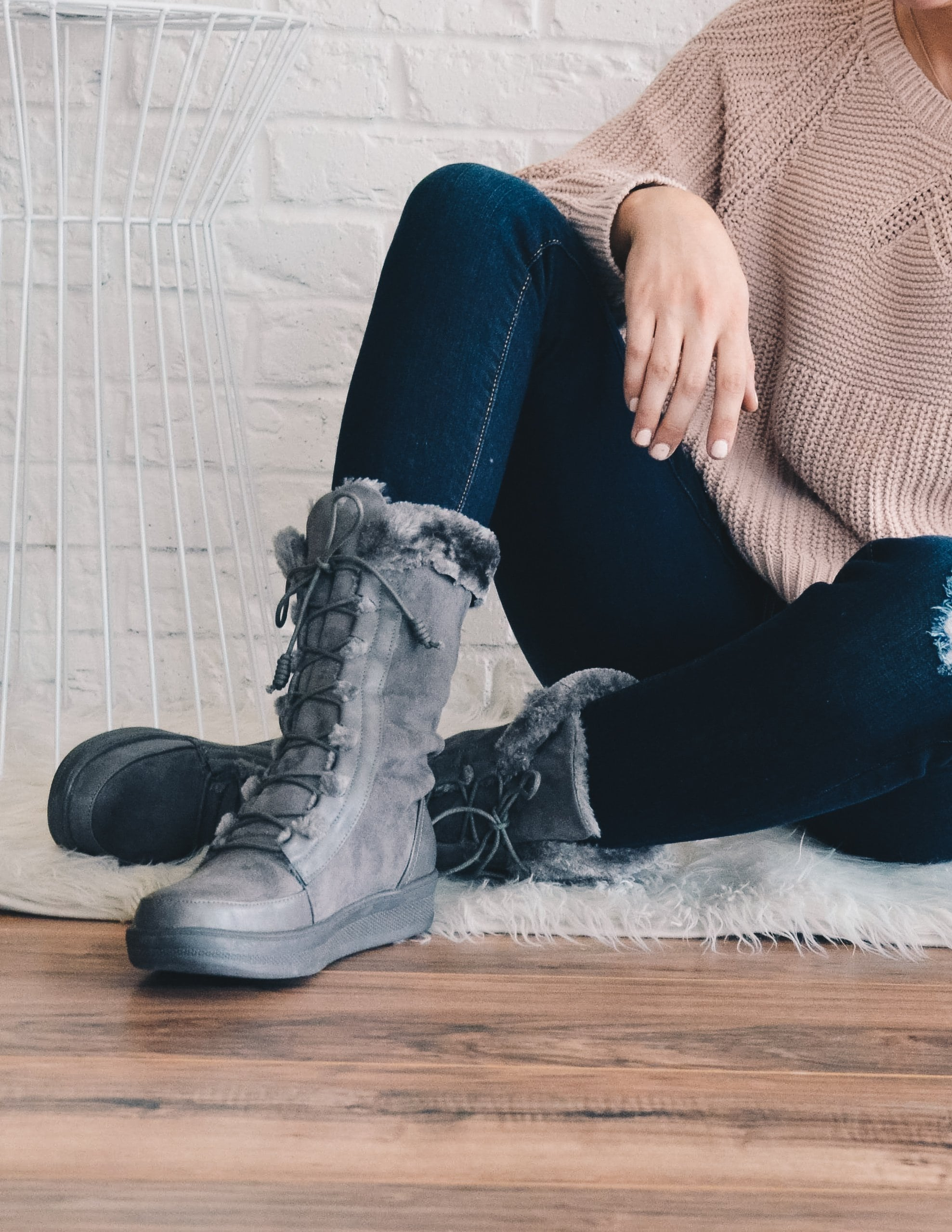 Girl sitting on floor crossing legs in denim and grey marshmallow boots