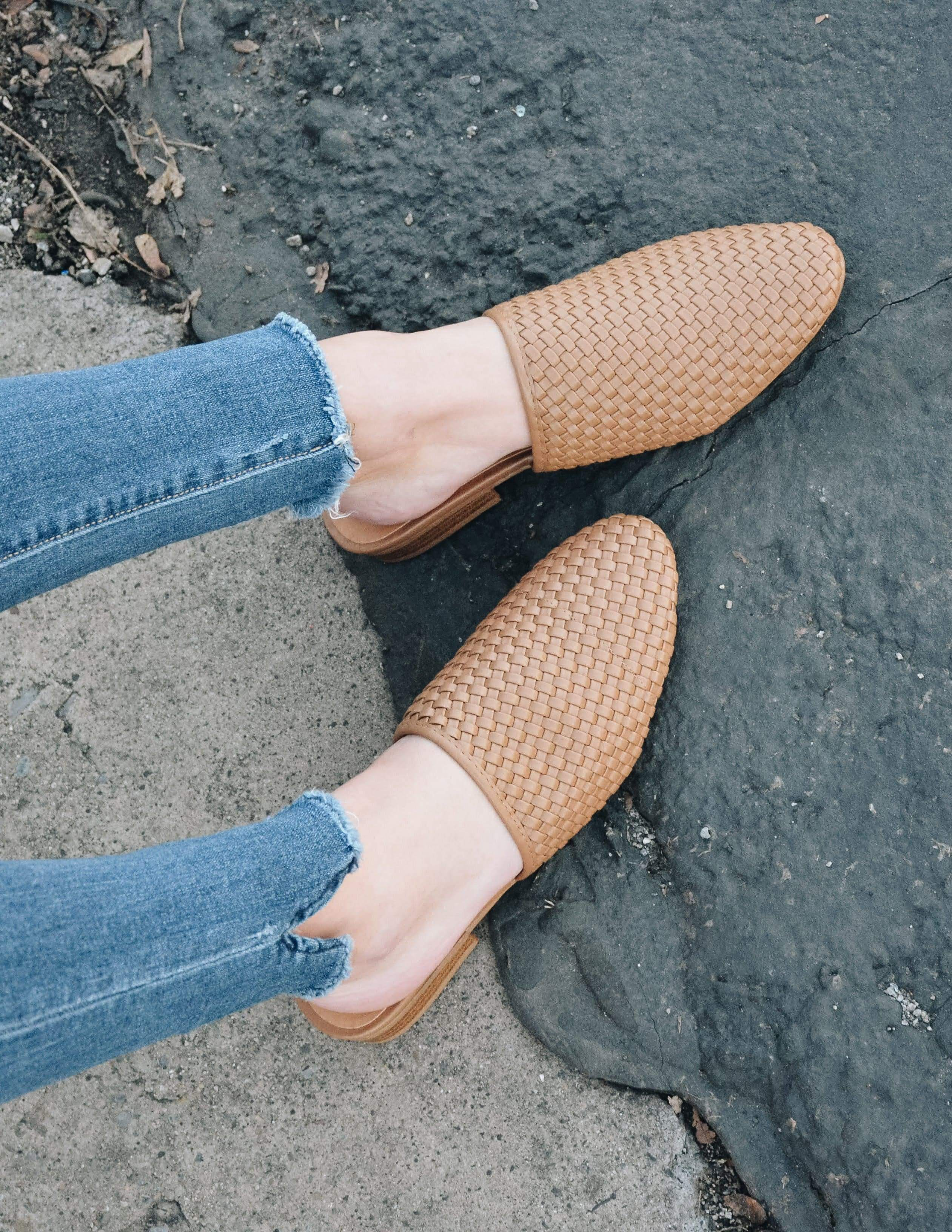 Closeup of the taupe woven lolli flat on model's feet outside - elle bleu