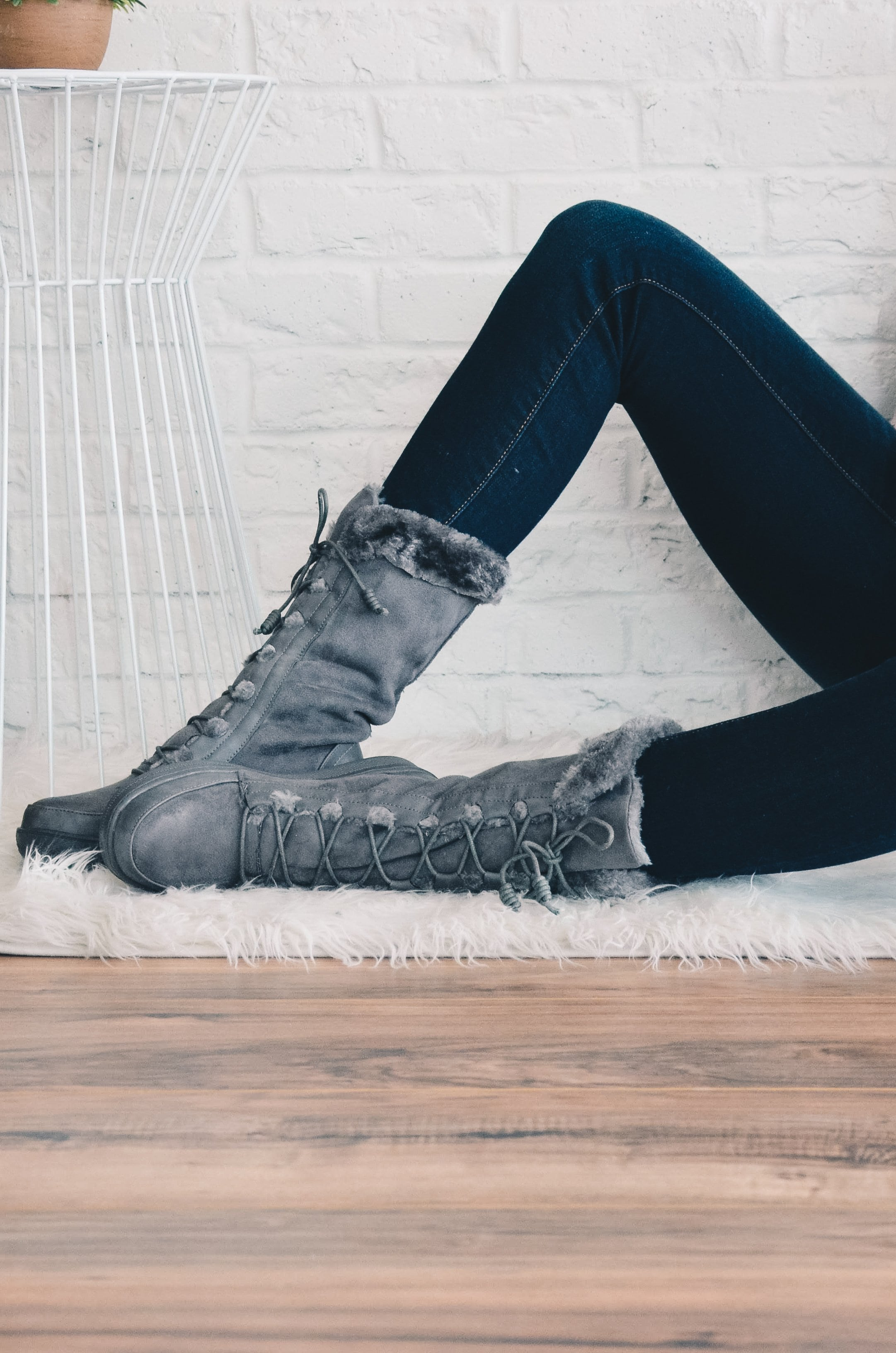 Model sitting in denim and grey fur marshmallow boots on wood floor