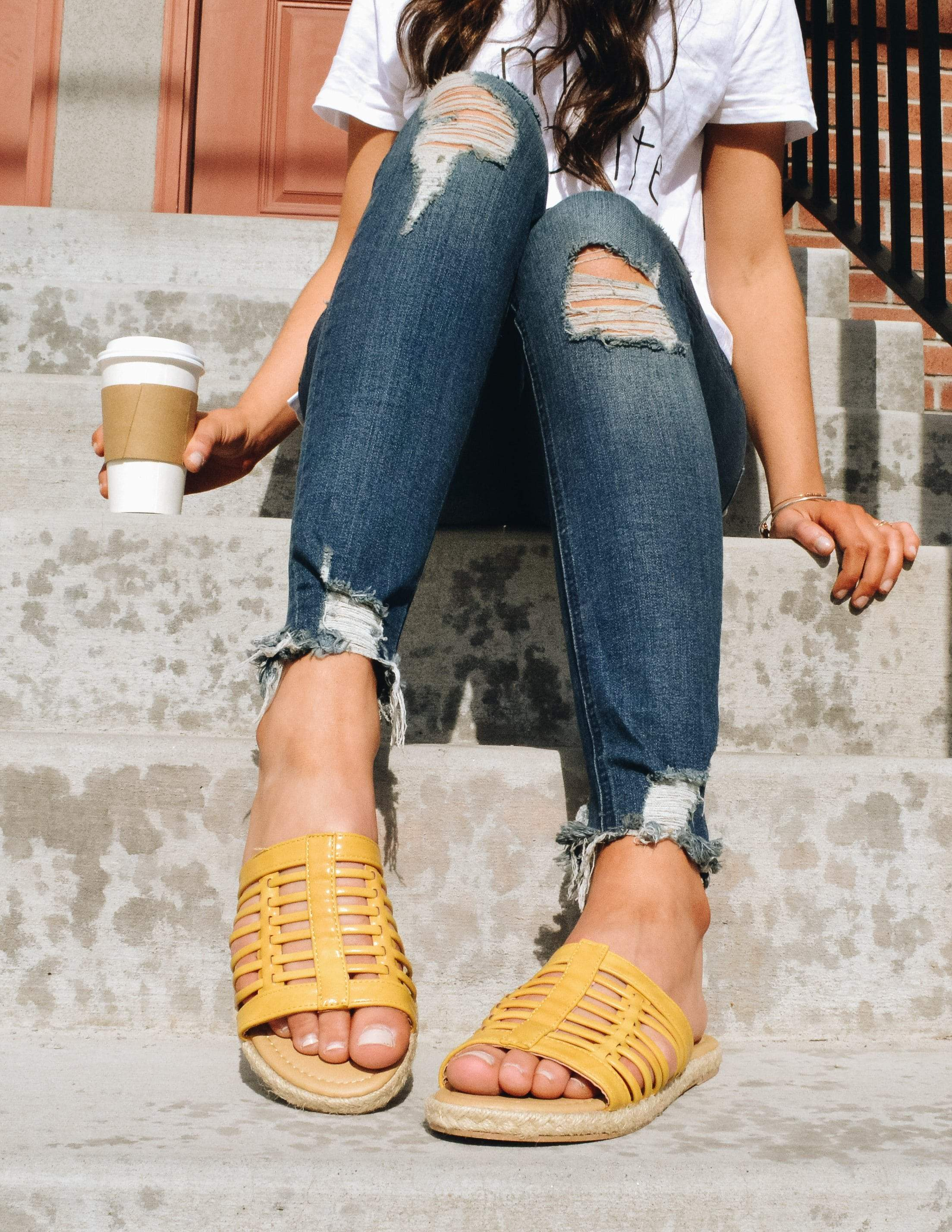 Model sitting on steps outside in tee, denim, and yellow sandals