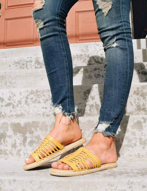 Knee down shot of model standing in denim and yellow surf's up sandal