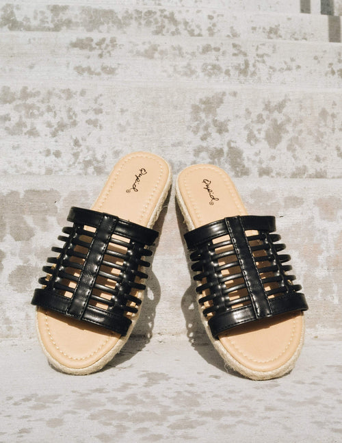Black strappy cage upper with light tan insole and rope trim sole