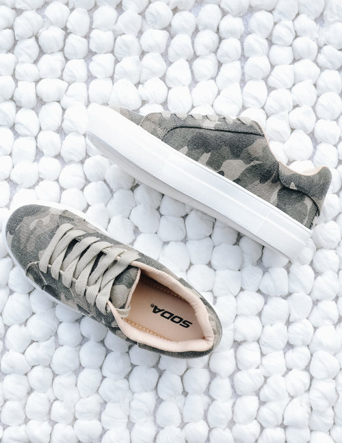 A lot of sole sneakers in camo on white rug - elle bleu shoes
