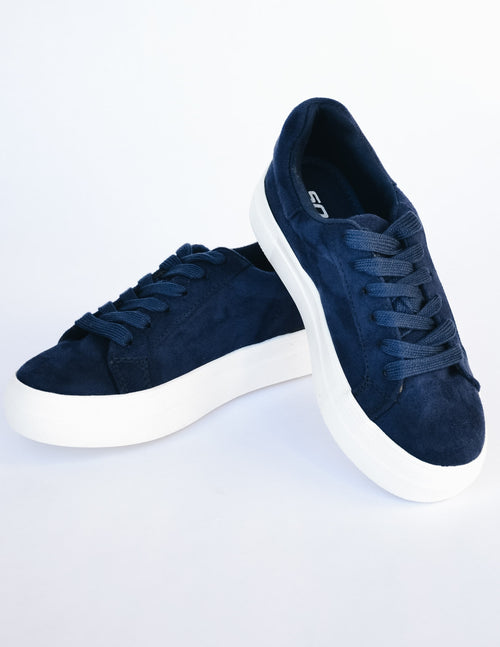 Navy sneaker stacked one heel on another on white background