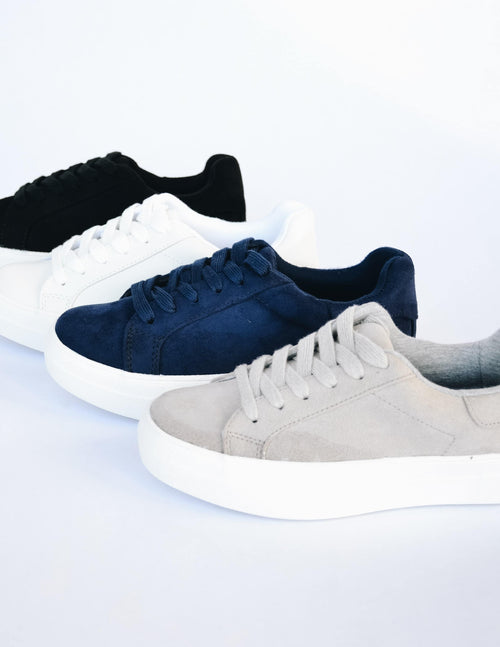 Black, white, navy, and smoke grey sneakers lined up on white background
