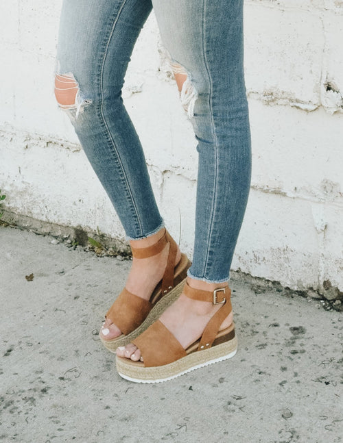 Girl standing outside in distressed denim and tan espadrille platform sandals