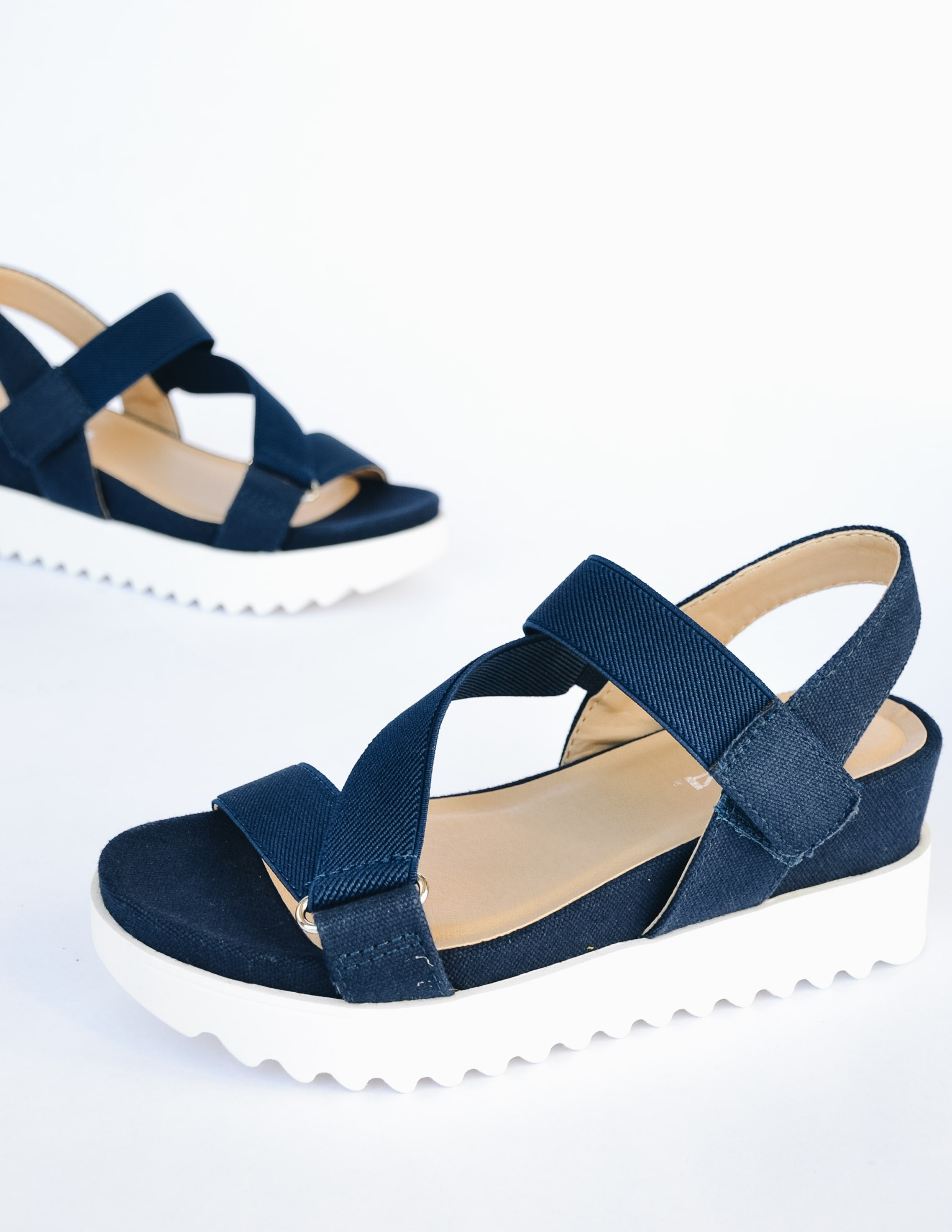 Wedge sandal with navy blue straps, tan insole, and white platform sole