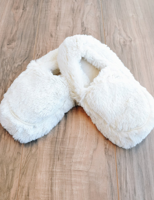 Creme faux fur warmies slippers on wood background - elle bleu