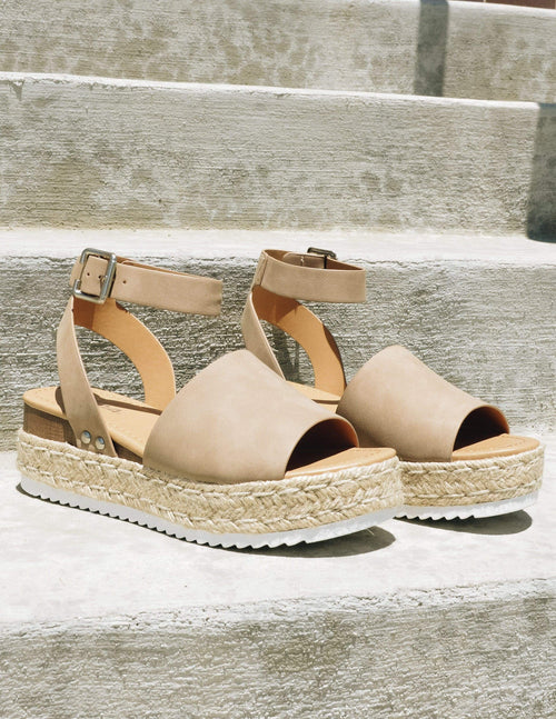 Taupe walkin' on sunshine platforms with white bottom outside on steps