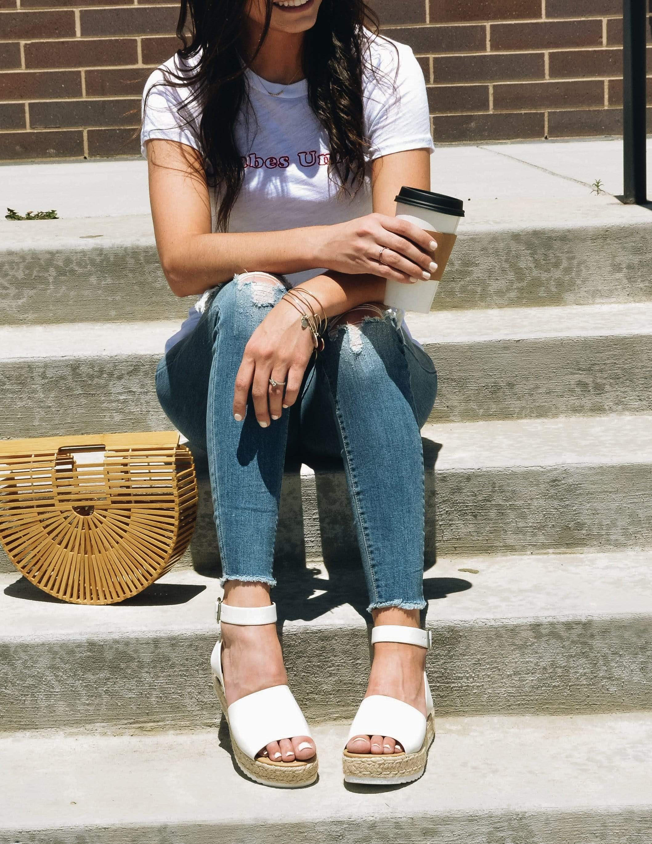 Brunette sitting on steps outside in denim and white tee holding coffee