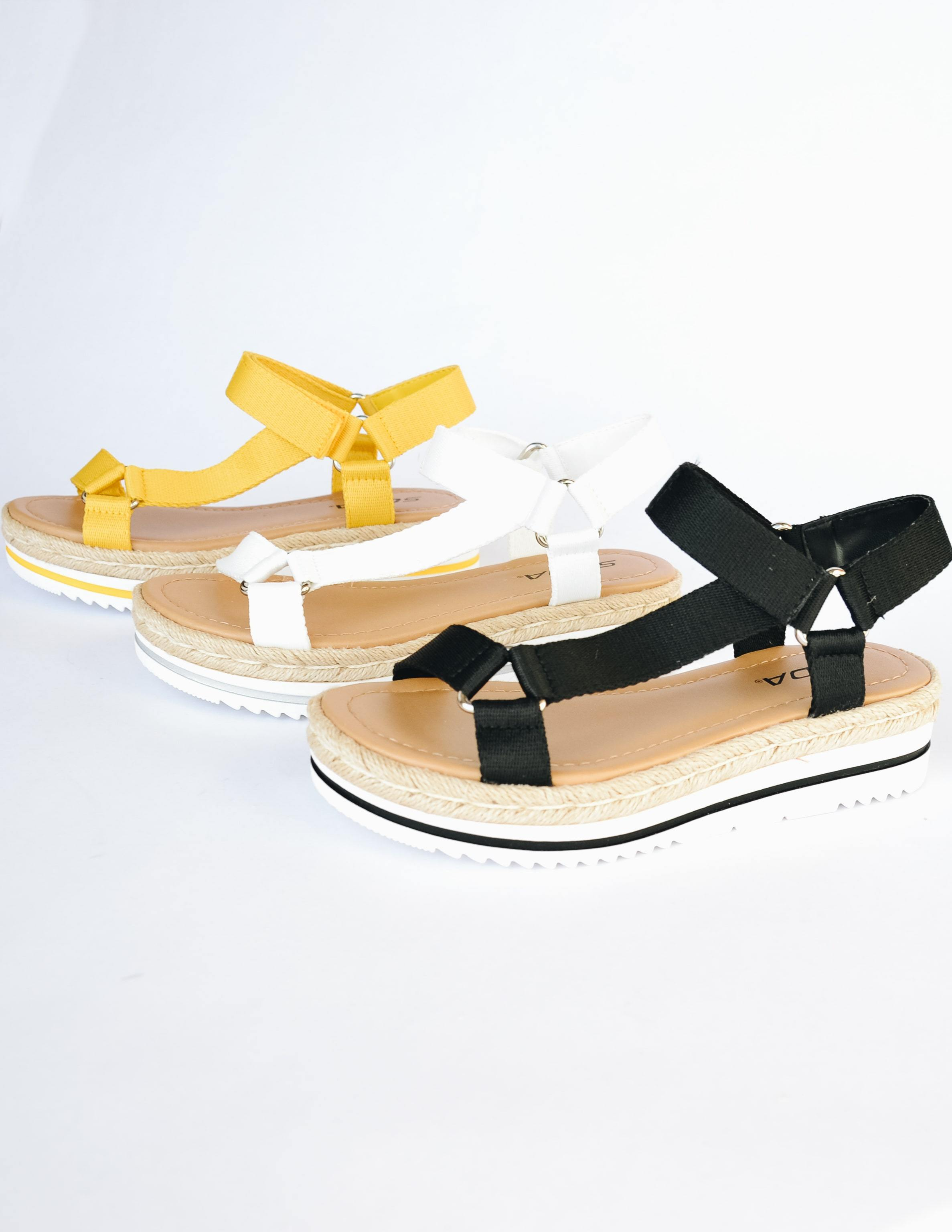 Yellow, white, and black good sport sandals lined up on white background