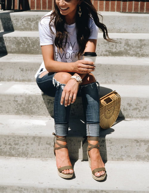 Brunette sitting on steps in tee, denim, green wedges holding coffee
