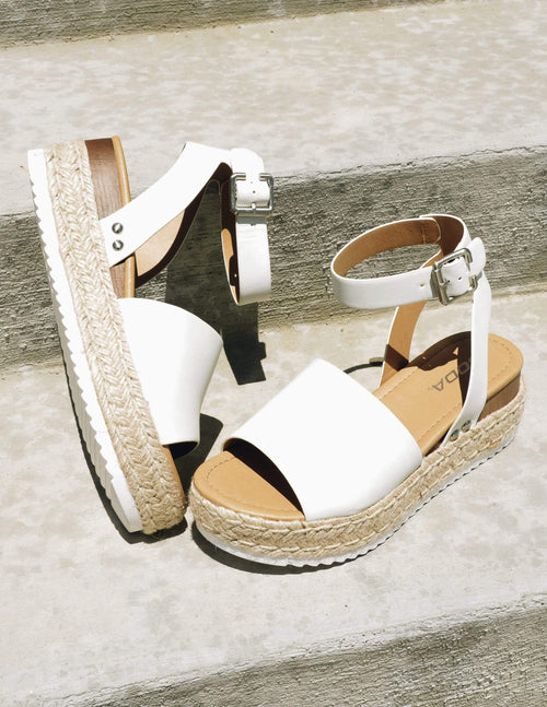 Off white platform sandal with rope trim, white bottom, and faux wood detail