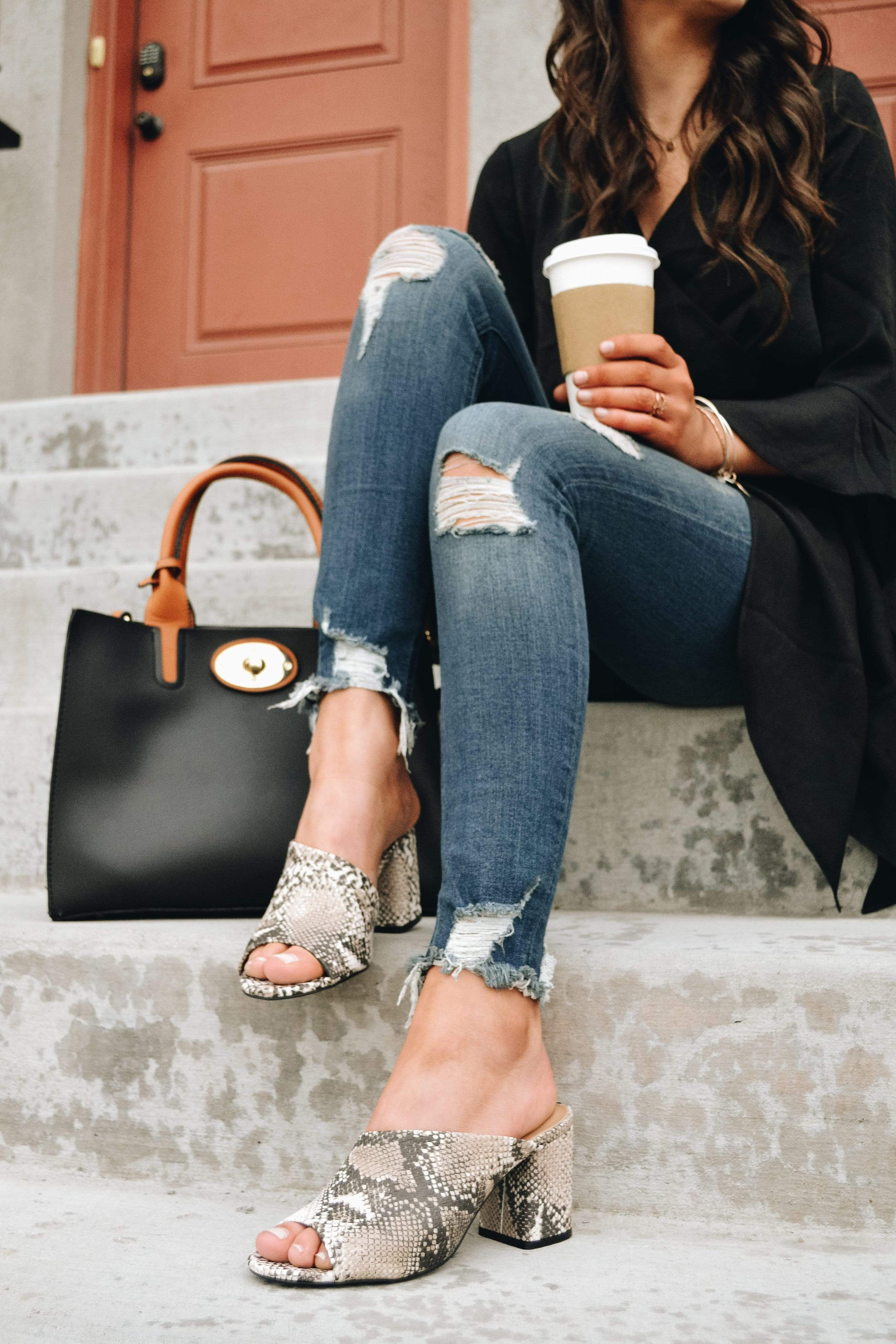 Model sitting on concrete steps holding coffee and wearing python heels