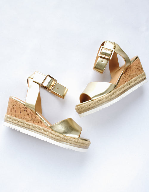 Gold wedge with faux cork sole and espadrille trim around bottom