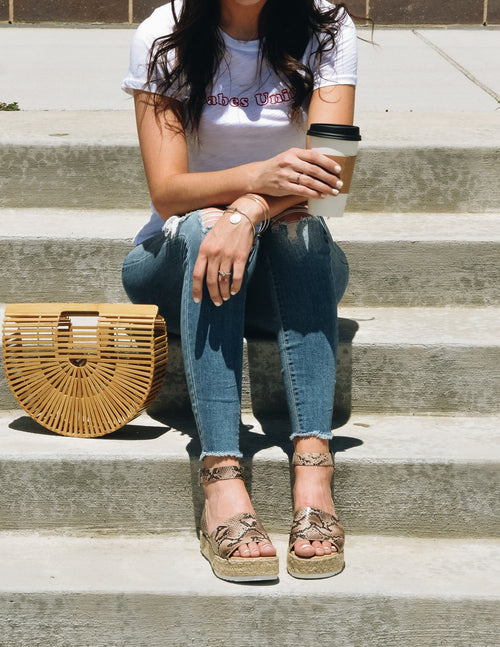 Girl sitting on steps in denim, tee, and snake print platforms - elle bleu